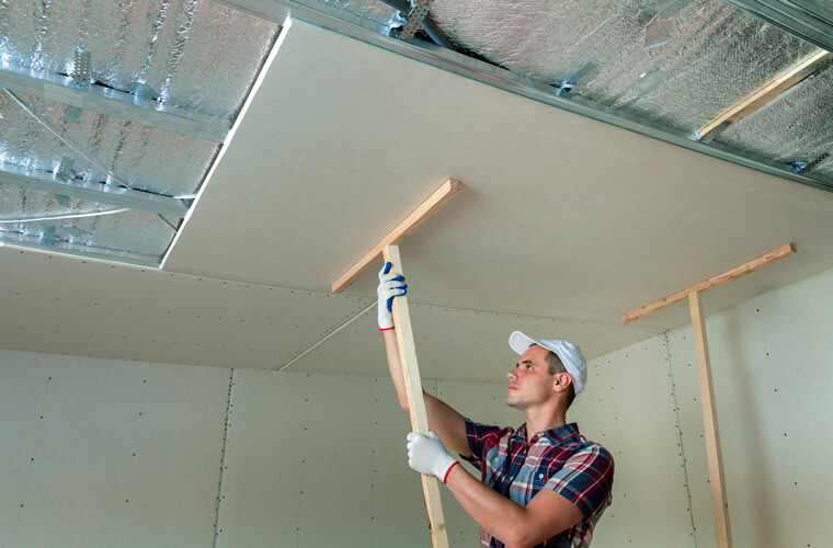 man hanging drywall on ceiling